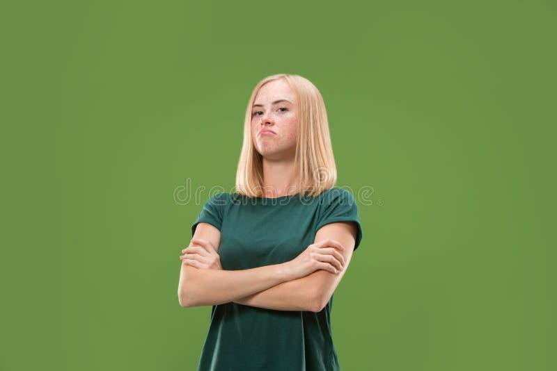 Suspiciont Donna pensierosa dubbiosa con l'espressione premurosa che opera scelta contro il fondo verde immagini stock