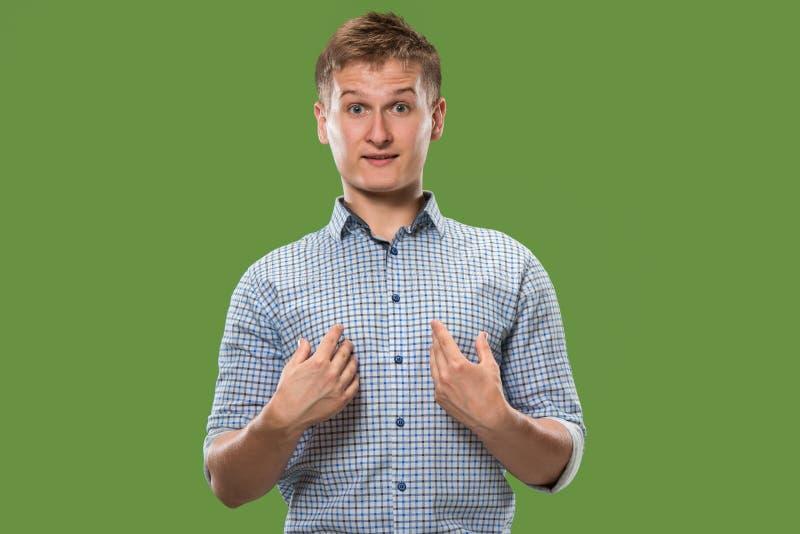 Suspiciont Hombre pensativo dudoso con la expresión pensativa que toma la decisión contra fondo verde foto de archivo