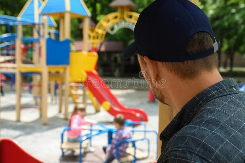 Suspicious adult man spying on kids at playground. Child in danger. Suspicious adult men spying on kids at playground, space for text. Child in danger stock images