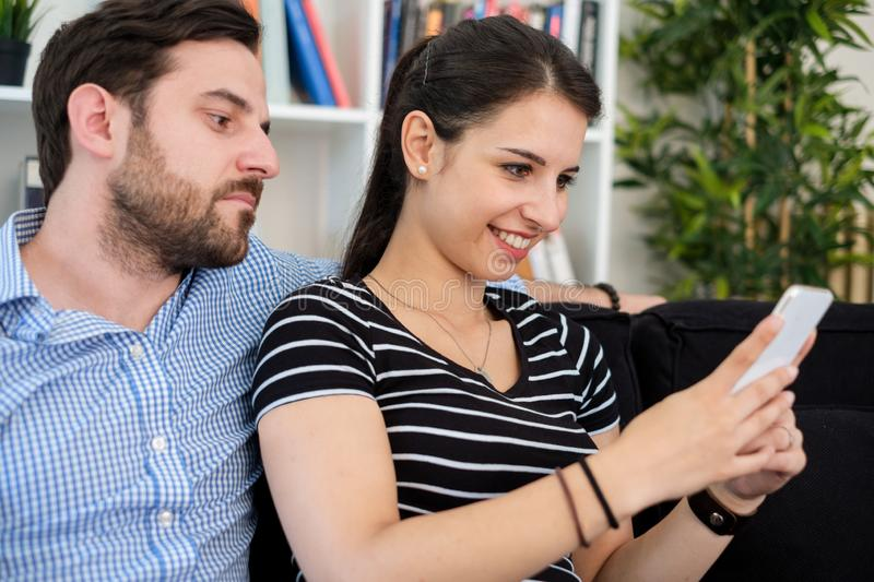 Suspicious boyfriend trying to read messages on the mobile phone of his girlfriend stock photography