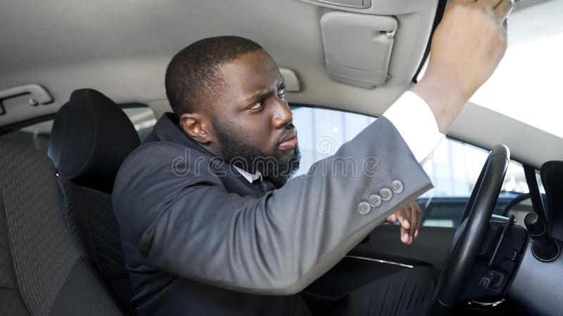 Suspicious business man looking in rear-view mirror, notices spy pursuit on road stock image