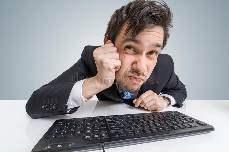 Suspicious businessman is looking at screen at work stock photos