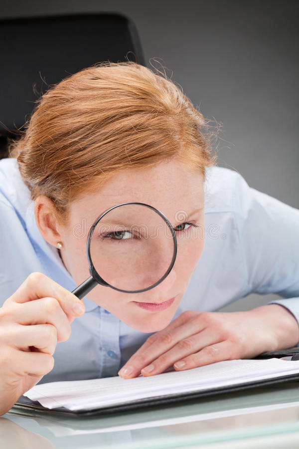 Suspicious Businesswoman. Suspicious female business leader with paperwork looking at the camera through a magnifying glass royalty free stock image