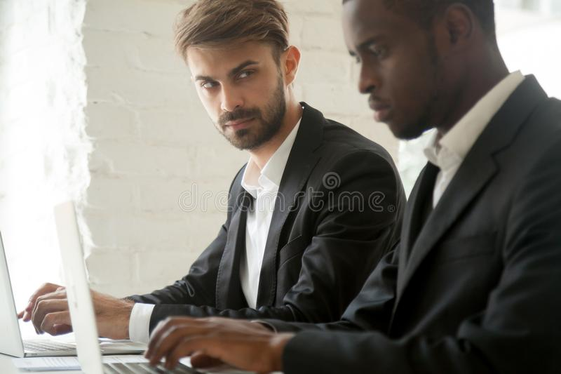 Suspicious Caucasian worker looking madly at busy black colleagu. Suspicious cunning male Caucasian worker looking at serious working African American colleague stock images