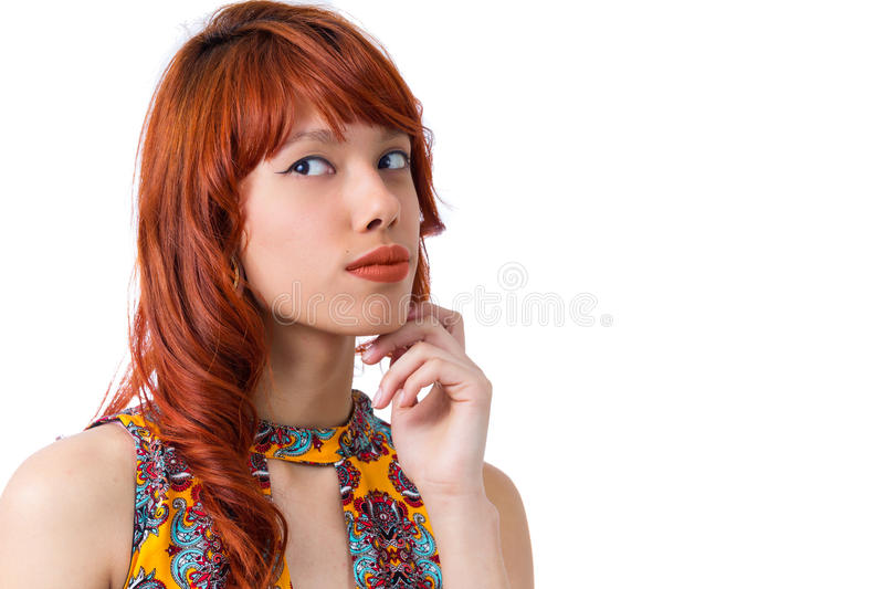 Suspicious girl looks to the side. Young redhead woman with summer dress.. stock images