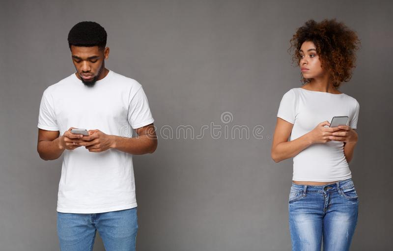 Suspicious jealous woman looking at her focused texting boyfriend royalty free stock images