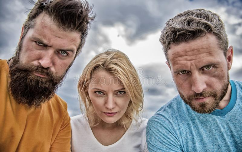 Suspicious look. They know what you did. Threesome suspiciously look down. Woman and men look confident sky background. Strength in unity. Stand up for their royalty free stock images