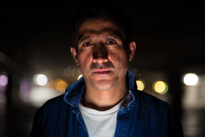 Suspicious-looking Hispanic man in dark parking lot. Portrait of suspicious-looking Hispanic man hiding in dark parking lot stock photography