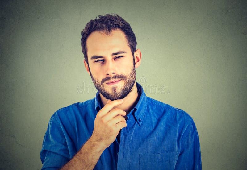Suspicious skeptical man. Portrait suspicious skeptical young man royalty free stock photo