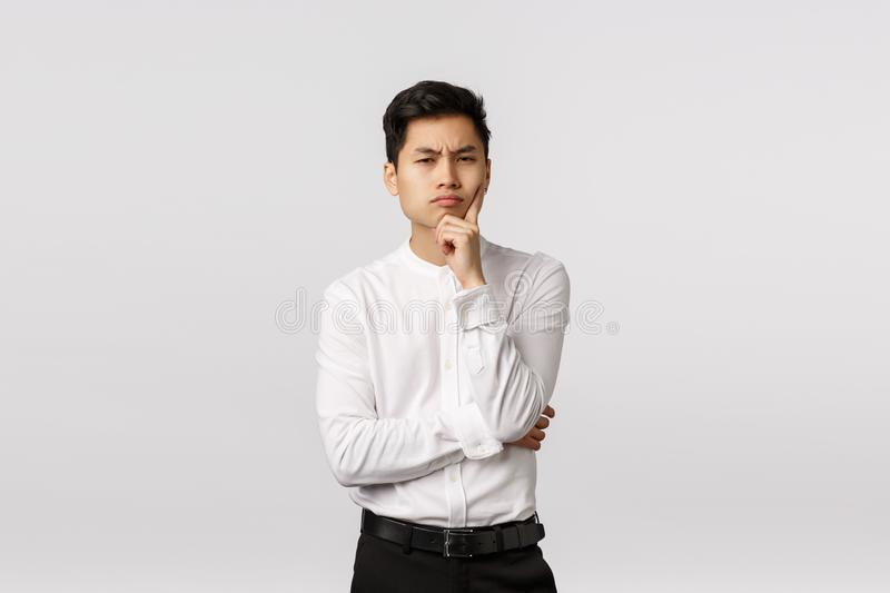 Suspicious and skeptical, thoughtful attractive asian man in shirt, pants, frowning look camera with disbelief and stock photos