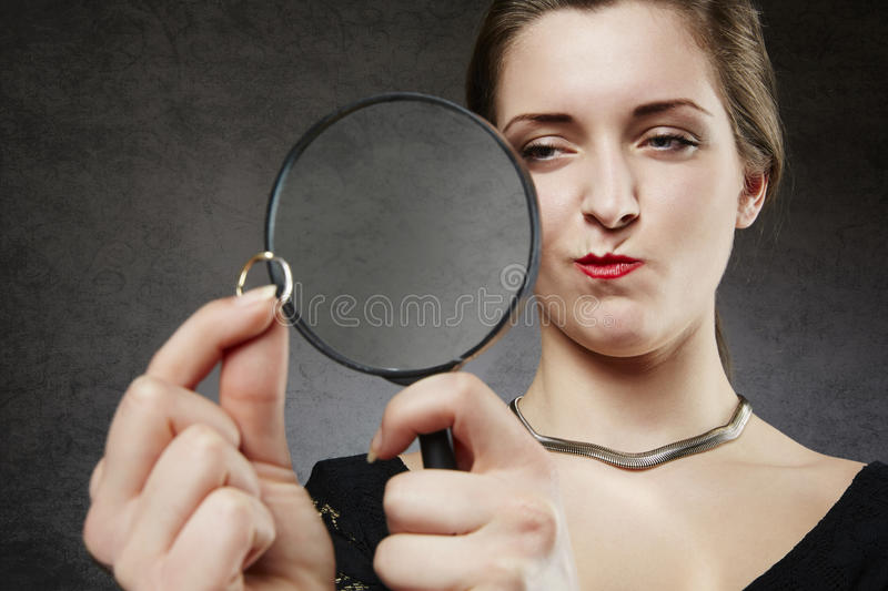 Suspicious woman looking at her wedding ring through magnifying glass stock image