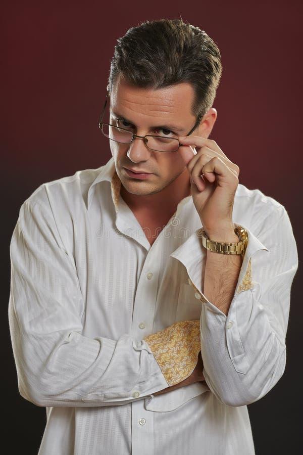 Suspicius man som ser över glasögon arkivfoton