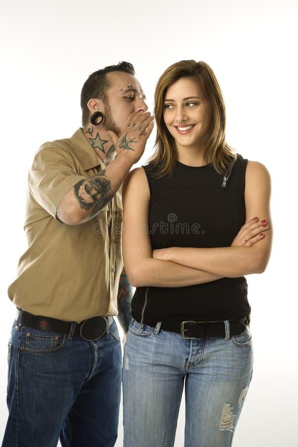 Sussurro maschio caucasico nell'orecchio della femmina teenager. immagini stock