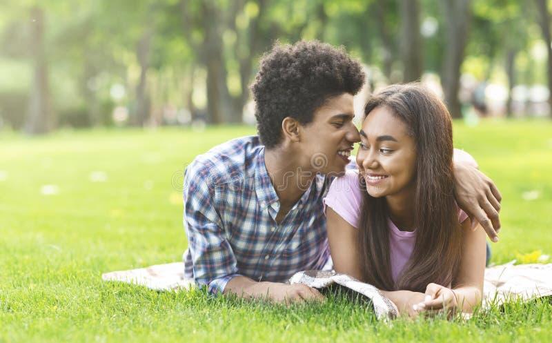Sussurro sobre o amor Adolescentes românticos que colocam na grama fora imagem de stock