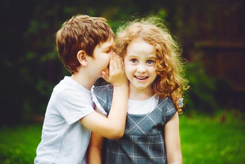 Sussurros do rapaz pequeno e da menina foto de stock