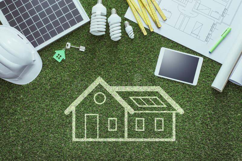 Green building. Sustainable house projects and green building concept: blueprint, solar panel and tools on lush grass stock images
