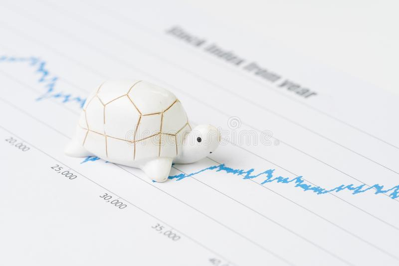 Sustainable with long term investment concept, miniature decorate turtle or tortoise slow walking on rising growth stock market v royalty free stock photo
