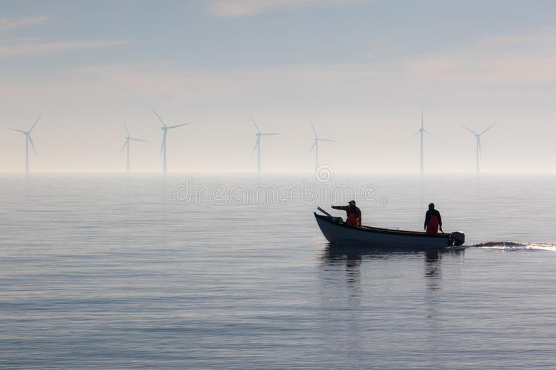 Sustainable resources. Small fishing boat heading out to sea stock photography
