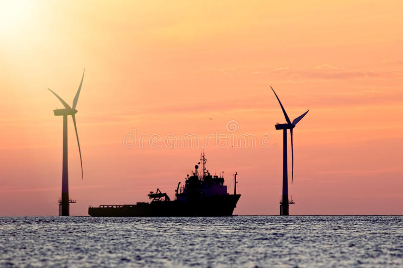 Sustainable resources. Wind farm with ship silhouette at tropical sunrise or sunset. Solar and wind energy and food supply. Represented in this tranquil image royalty free stock photo
