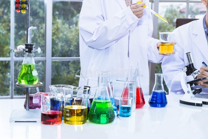 Sustancias de mezcla del estudiante femenino joven del científico en tubo de ensayo foto de archivo