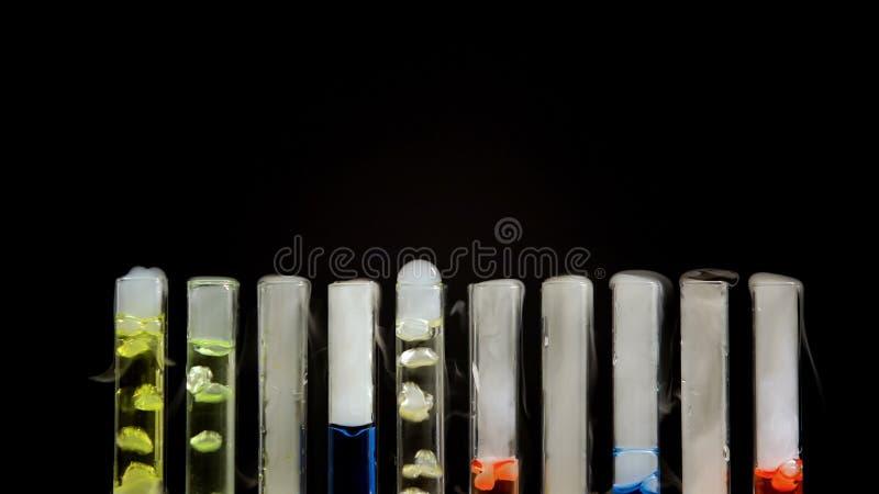 Sustancias narc?ticas multicoloras con las burbujas en tubos de ensayo en fondo negro imagenes de archivo