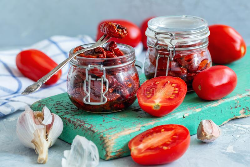 Suszący pomidory z czosnkiem, pikantność i oliwa z oliwek, obrazy stock
