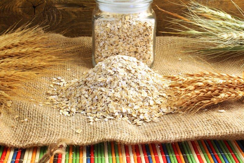 Suszę staczał się oatmeal płatki w butelce na jutowym płótnie z owsów ucho i obraz royalty free