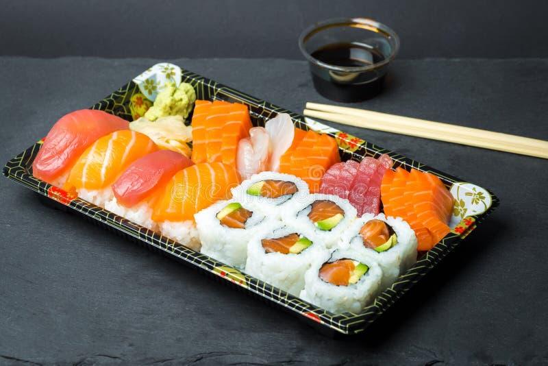 Suszi i Sashimi rolki na czarnym kamiennym slatter Świeży robić suszi ustawiający z łososiem, krewetkami, wasabi i imbirem, Trady obraz royalty free