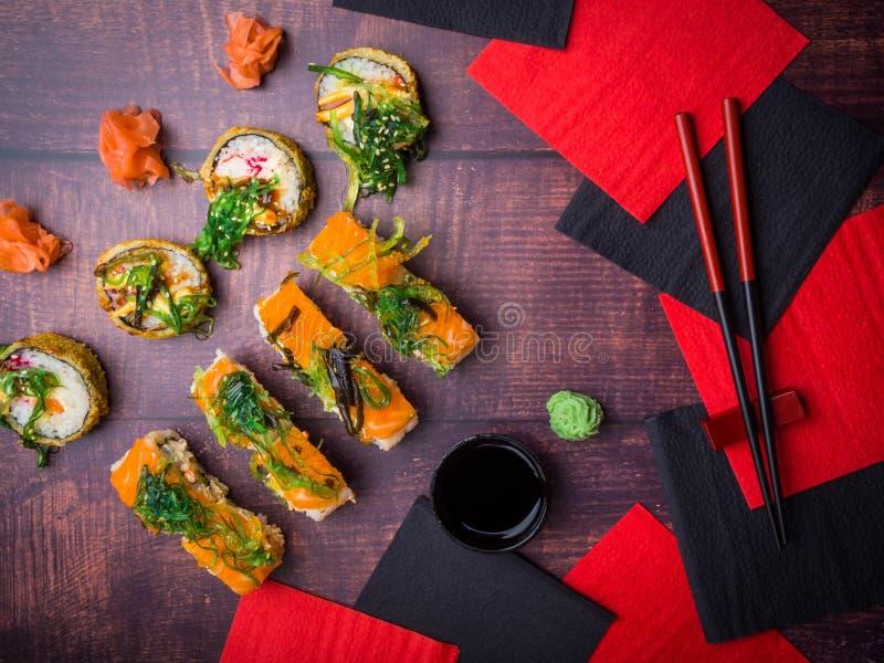 Suszi z chopsticks soj kumberlandem, wasabi, imbir, wakame na drewnianym tle obraz stock