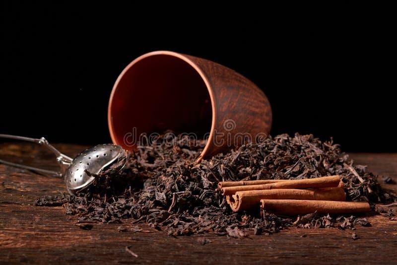 suszy czarnego chińskiego herbata set z durszlaka zbliżeniem, filiżankami i teapot na tle nad starą drewno deską, obraz stock