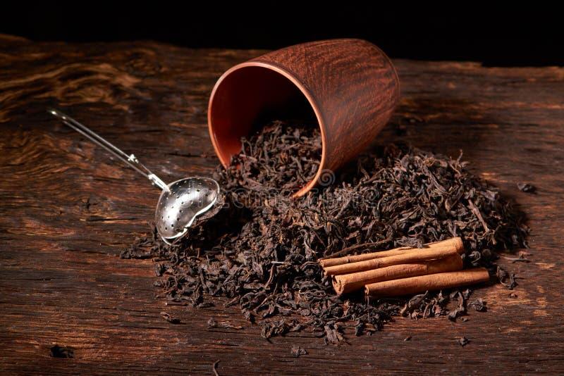 suszy czarnego chińskiego herbata set z durszlaka zbliżeniem, filiżankami i teapot na tle nad starą drewno deską, zdjęcia stock