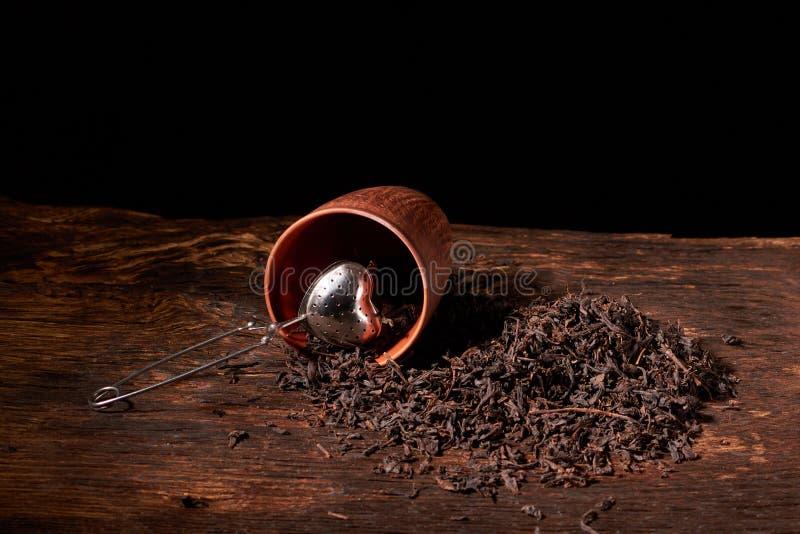 suszy czarnego chińskiego herbata set z durszlaka zbliżeniem, filiżankami i teapot na tle nad starą drewno deską, zdjęcie stock