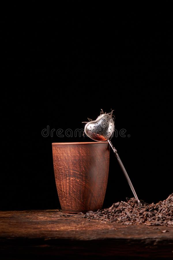 suszy czarnego chińskiego herbata set z durszlaka zbliżeniem, filiżankami i teapot na tle nad starą drewno deską, fotografia stock