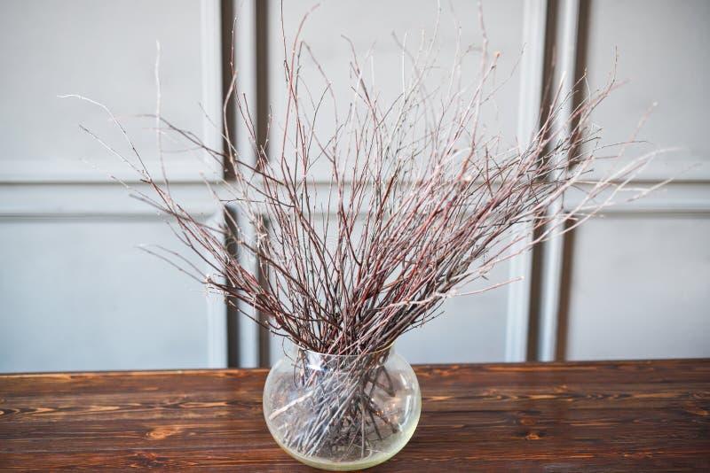 Suszy gałąź w przejrzystej wazie na drewnianym stole, szary tło obrazy stock