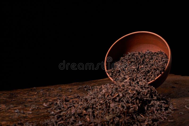 Suszy herbacianych liście w glinianym pucharze na czarnym tle Selekcyjna ostrość zdjęcia royalty free