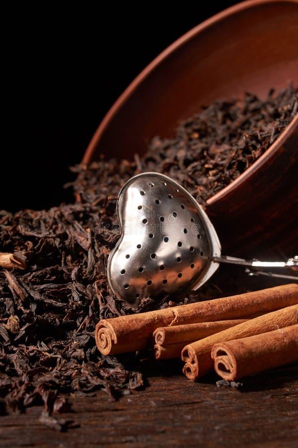 Suszy herbacianych liście w glinianym pucharze na czarnym tle Selekcyjna ostrość zdjęcie stock