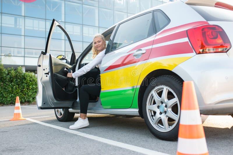 Sutdent få för kvinnlig chaufför ut ur bilen fotografering för bildbyråer