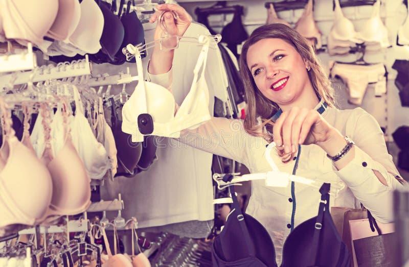 Sutiãs de exame de sorriso do cliente fêmea na loja imagem de stock