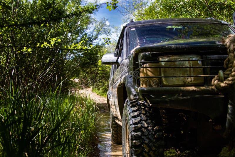 SUV有4 x 4的越野车在泥泞的轨道的路 库存照片