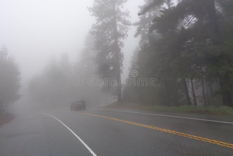 SUV που ταξιδεύει στον ομιχλώδη δρόμο βουνών στοκ φωτογραφία