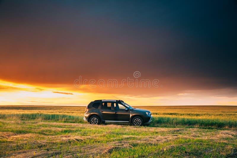 雷诺喷粉器或达基亚喷粉器Suv在路通过夏天麦田在令人惊讶的日落时间 共同地被生产的喷粉器  免版税库存照片