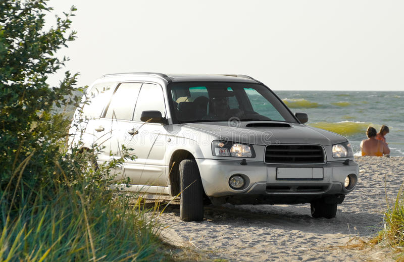 SUV. Stands on the beach on the background of the sea royalty free stock image