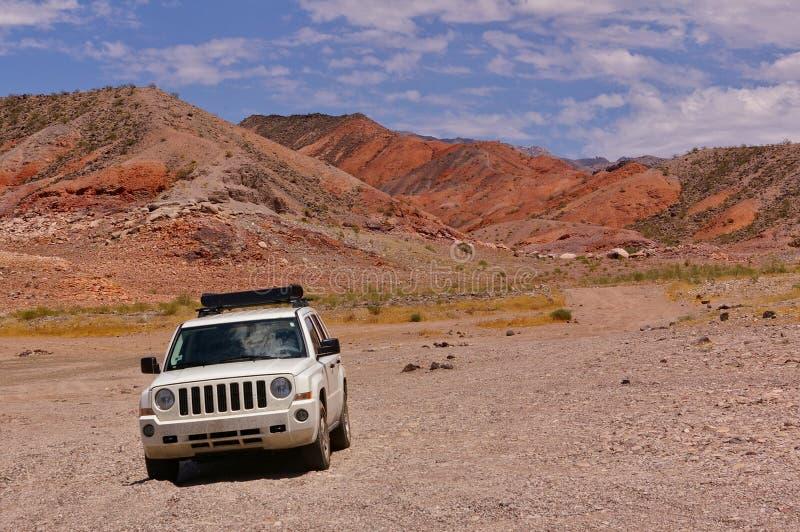 SUV blanc sur la traînée à distance de désert avec les collines rocheuses à l'arrière-plan photo libre de droits