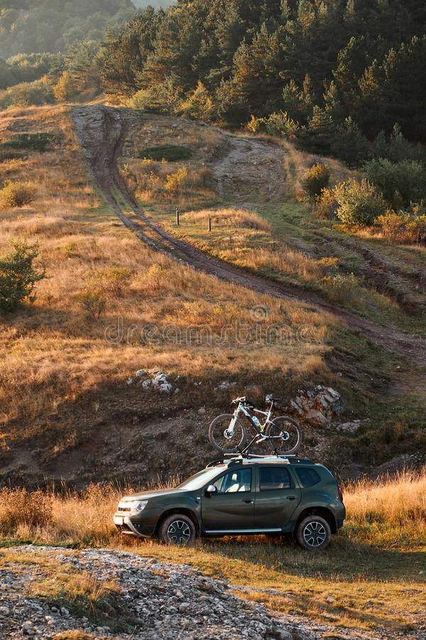 Suv car with bicycle on the roof top at country road near the forest. vertical. stock images