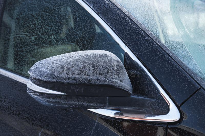 SUV car mirror covered with fresh frost. In cold winter season royalty free stock image