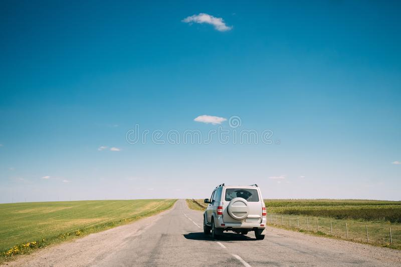 SUV Car Mooving Along Road In Spring Summer Fields Landscape. Drive. Gray SUV Car Mooving Along Road In Spring Summer Fields Landscape. Drive And Travel Concept royalty free stock photo