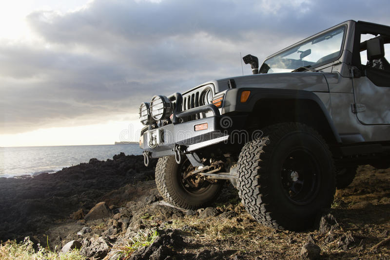 SUV at Coast. Low angle view of front of SUV on a rocky beach. Horizontal format stock photo