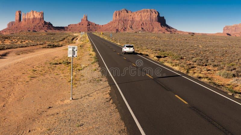 SUV conduce hacia el valle del monumento en la frontera de Utah/de Arizona, Americ fotos de archivo