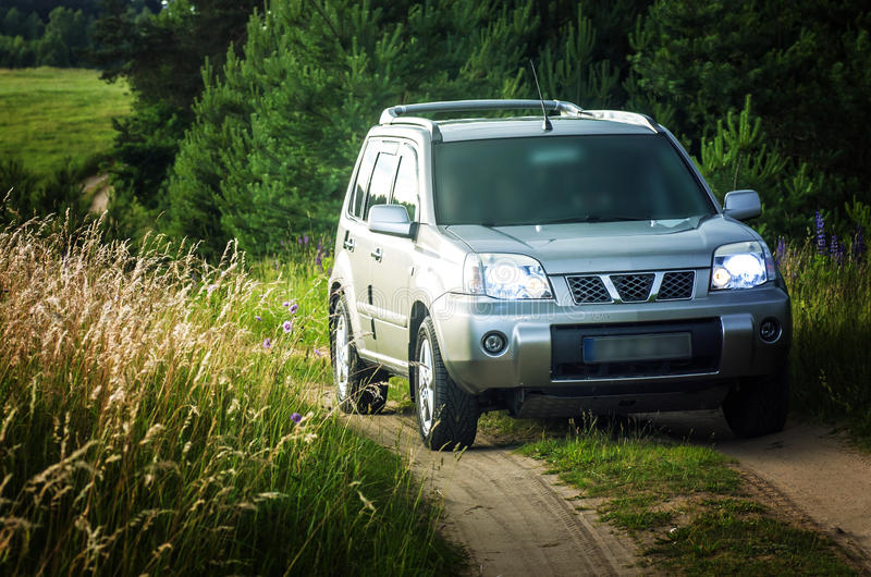 Suv in countryside. Nissan X-trail in the forest path stock photo