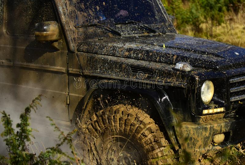 SUV covered with dirt on nature background. Part of car and cloud of smoke. Vehicle covered with mud. Off road racing. Force and extreme entertainment concept royalty free stock image